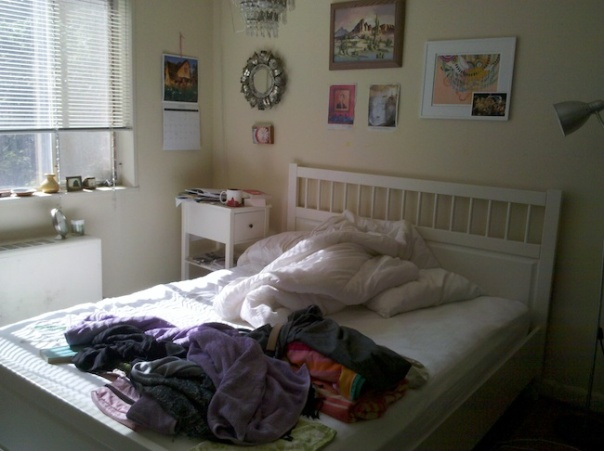 Bed with white sheets and colored towels