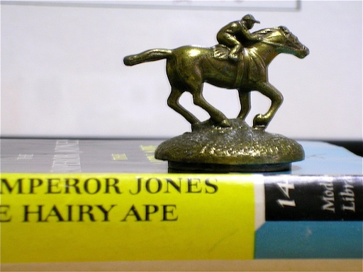 small brass figurine of horse and jockey on top of yellow book