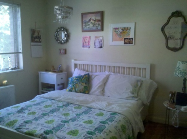 White IKEA queen size Malma bed with green print coverlet and white pillows and several artworks on the wall