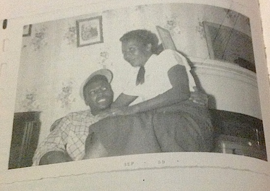 A black woman sits on an black man's lap